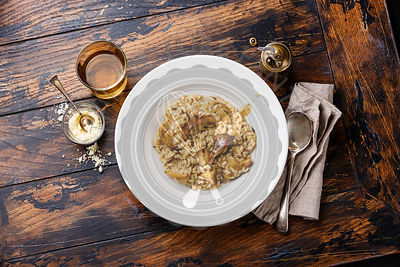 Risotto with porcini mushroom on plate on wood table background