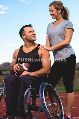 Handsome man in wheelchair talking with attractive young woman