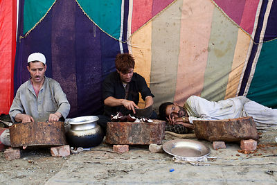 India - Srinagar - A Waza, a traditional Kashmiri cook, chops ingredients whilst his exhausted companion sleeps after cooking...