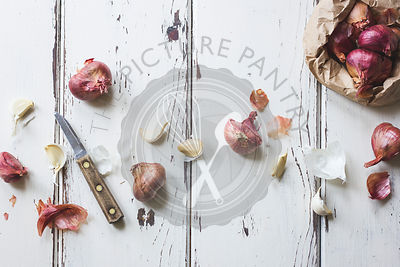 Shallots and Garlic, with Knife on White Wood
