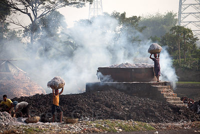 Workers carry baskets of leather scraps to be incinerated near the town of Bantala, East Kolkata Wetlands, Kolkata, India. Th...