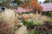 Gravel path leading into the central circular bed framed by miscanthus, rosemary, Stipa gigantea, salvias, Sedum 'Purple Empe...
