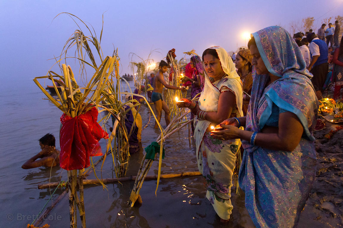 Ladies pray at sunset along the Ganges River during Chhath Puja, Varanasi, India. Chhath Puja is a devotion to the Sun God Su...