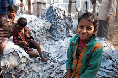 "Girls sit on piles of leather in a ""slum"" in Chamrapatti, Kolkata, India. Leather tanning for handbags and purses is the main..."