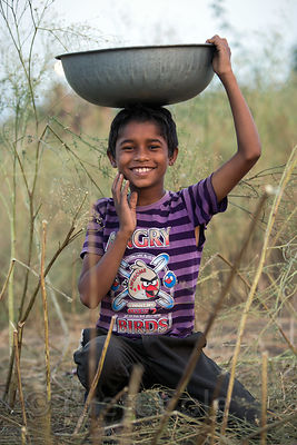 A boy wearing an Angry birds t-shirt collects camel dung for fuel in the Thar Desert in Pushkar, Rajasthan, India