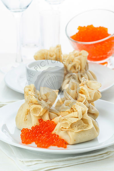 Pancake pouches with red caviar on white background
