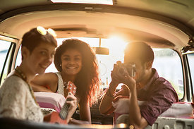 Mixed group of happy young people in a car having fun