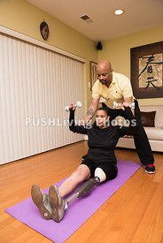 Woman with a prosthetic leg on an exercise mat stretching and lifting weights