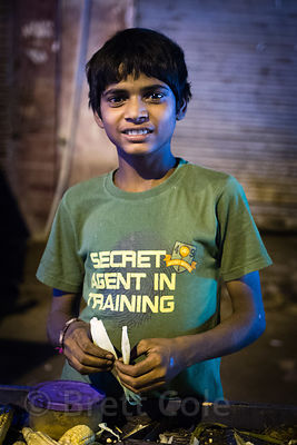 Secret Agent in Training. A boy sells fire-baked corn at night at his father's roadside cart in Paharganj, Delhi, India