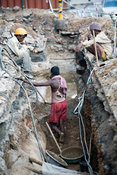 India - Delhi - Construction workers take a tea break in a ditch