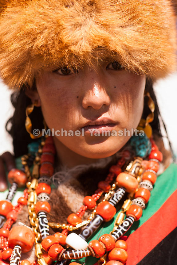 A young girl's finery comes out for the festival, from red fox fur hat to layers of ornate jewelry.