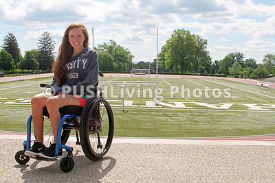Young woman in a wheelchair at a campus sports ground