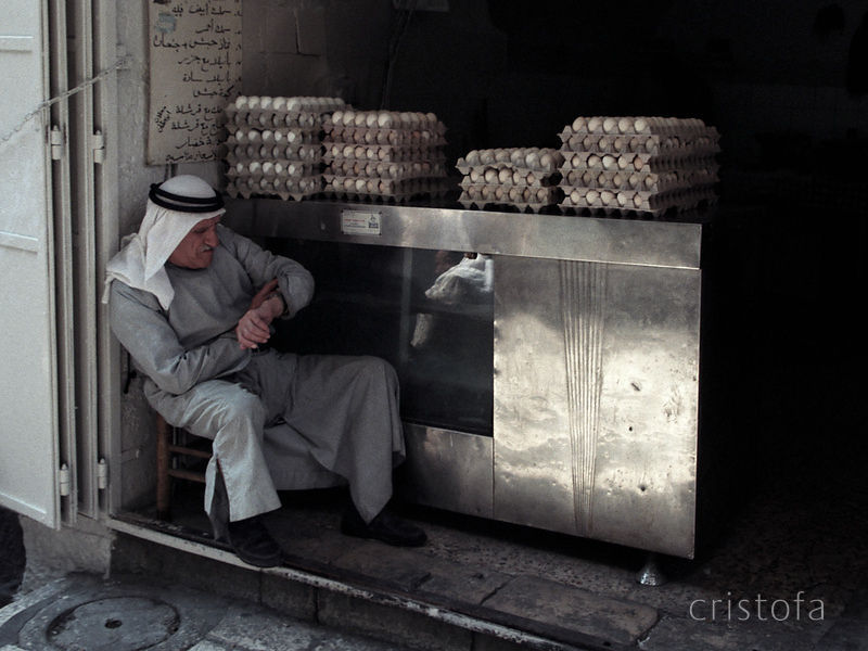 egg seller in Jerusalem checks the time