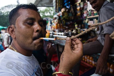 A man lights a cigarette using the smoldering end of a piece of dense rope, Newmarket, Kolkata, India