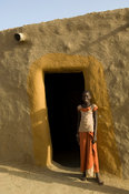 Girl at the entrance of a typical mud house, île à Morphil, Senegal