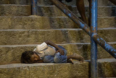 A homeless boy sleeps on a step at night while people walk past him, Dashashwamedh Ghat, Varanasi, India.