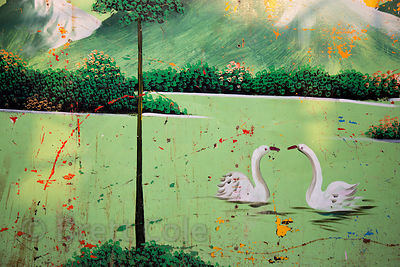 Weathered painting of swans on a carnival ride, Pushkar, Rajasthan, India