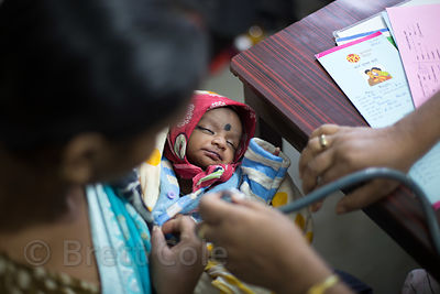 A infant has her heart checked at a clinic in Howrah, India