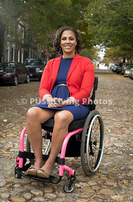 Young woman in a wheelchair in an old leafy cobblestoned city street