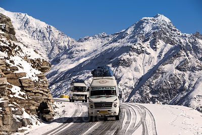 Tourist buses ply the sketchy, icy road at the summit of Rohtang Pass, Manali, India. The summits in the background are about...