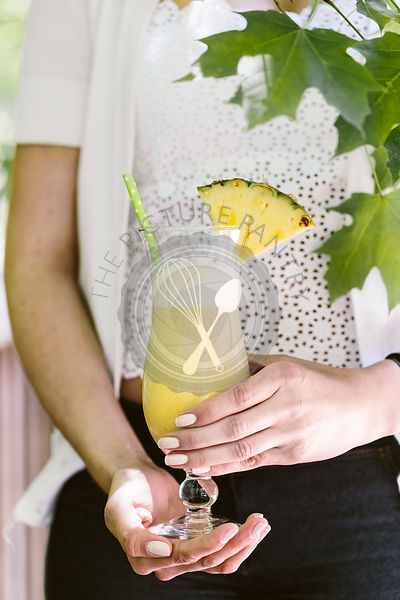 A woman holds a pina colada cocktail