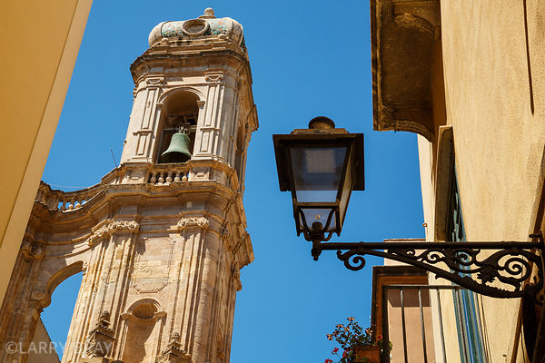 Bell tower and lamp against blue sky in Trapani, Sicily, Italy