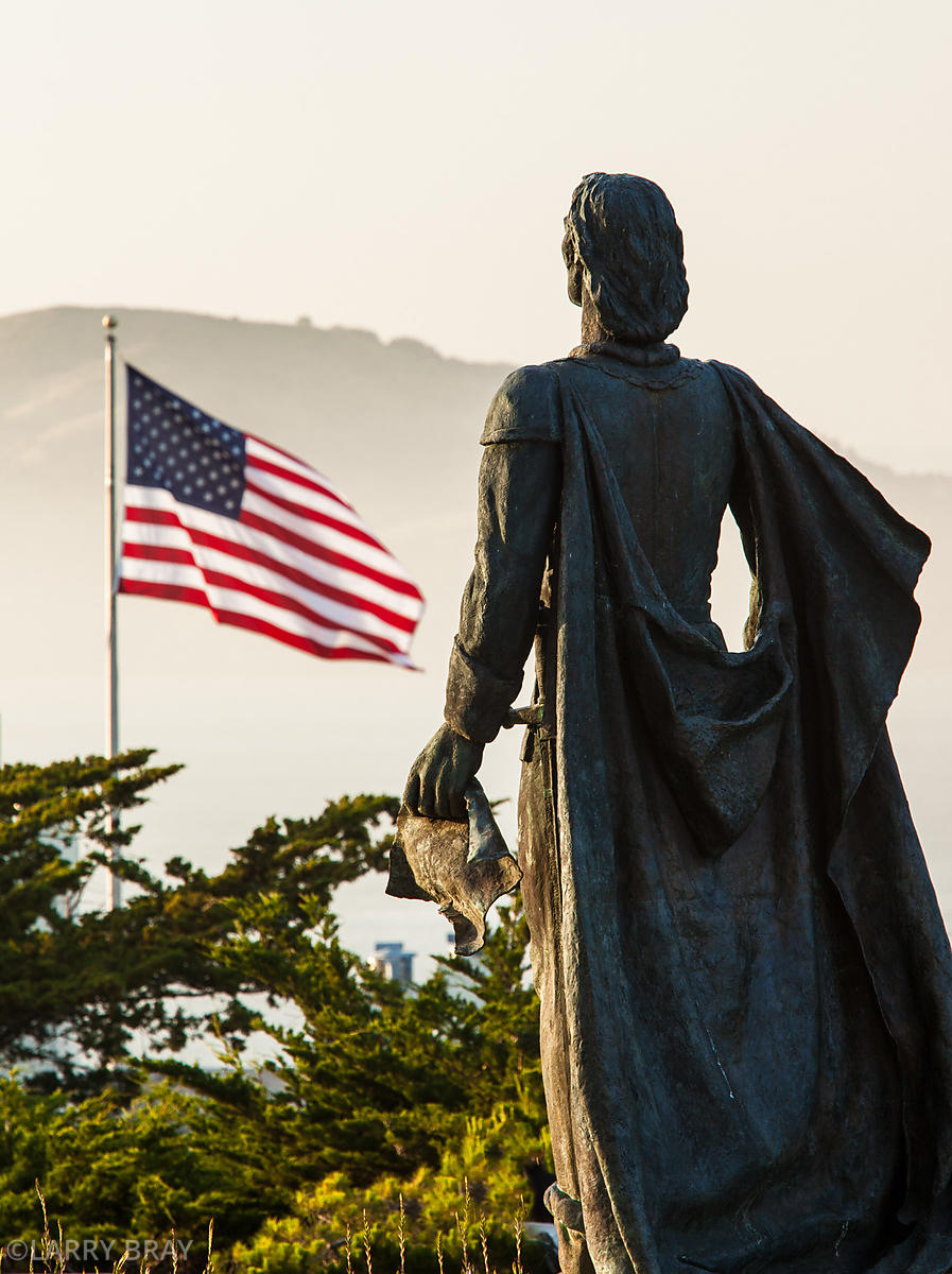 Statue of Christopher Columbus looking towards American flag  near Coit Tower in San Francisco, California, USA