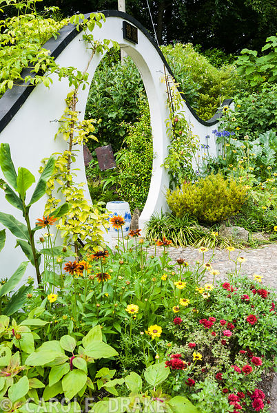 Moon gate marks passage from the kitchen garden to the Wandering Garden, framed by trained fruit trees, rudbeckias, agapanthu...