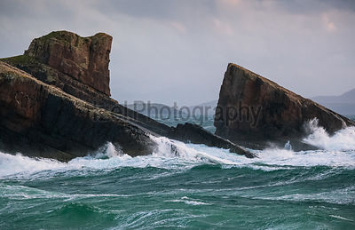 Split Rock is being pounded by the waves as bad weather approaches.. Clachtoll Bay, North West Highlands of Scotland.