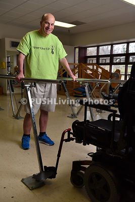 Man using parrallel bars in a rehabilitation gym