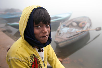 A boy from a fishing family poses by his father's boat on the Ganges River, Varanasi, India.