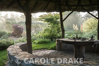 View of garden framed by thatched African style hut. Westonbury Mill Water Garden, Pembridge, Herefordshire, UK