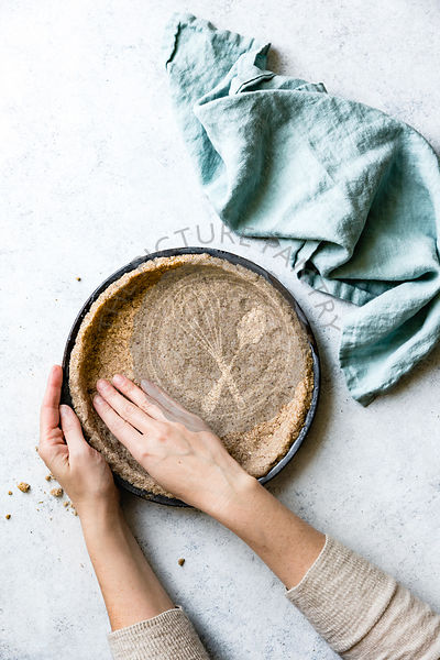 Hands preparing a pie base with alternative healthy flours