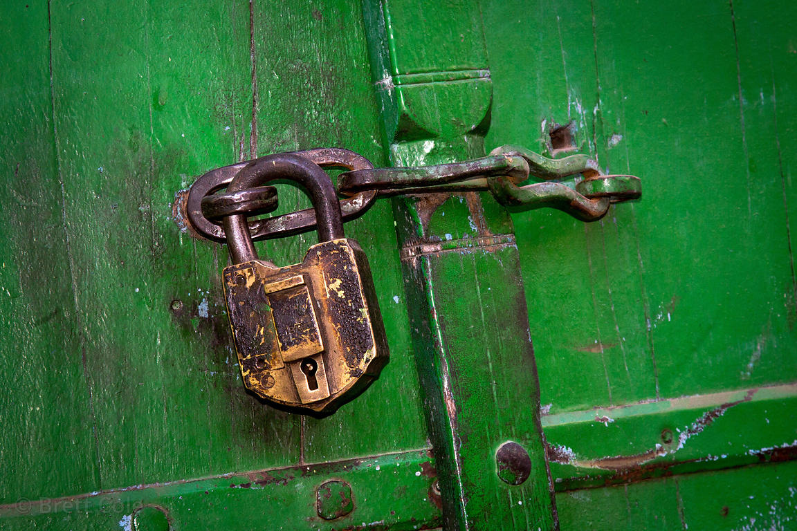 Weathered old lock on a bright green door, Pushkar, Rajasthan, India