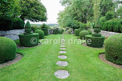 Topiary garden features clipped box shapes either side of a lawn with circular stepping stones leading southwards to the Whit...