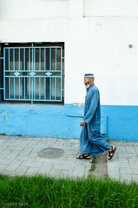 Local man in blue robes walking in street in Algiers, Algeria, North Africa