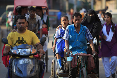 A muslim girl is driven to school in a cycle rickshaw in Delhi, India