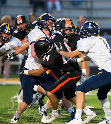 Iowa City Regina's Scott Blondin (14) is tackled by Solon's Ryan Geistkemper (44) during the first half of play in Solon on F...