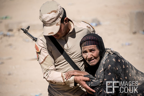 Iraqi Soldier supports an old woman as she arrives at a field hospital having escaped from her home in Mosul. Mushaarifa, Mos...
