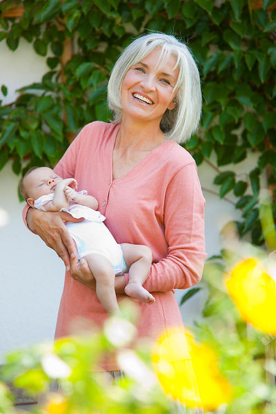 Germany, Bavaria, Woman with grandchild in her garden, smiling