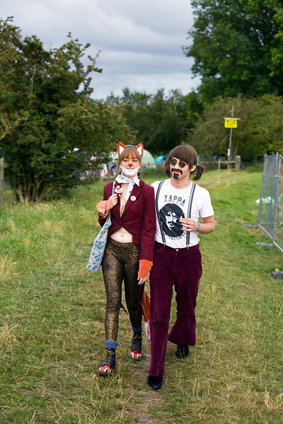 UK - Standon - A couple in costume walk through the camping field at the Standon Calling Festival