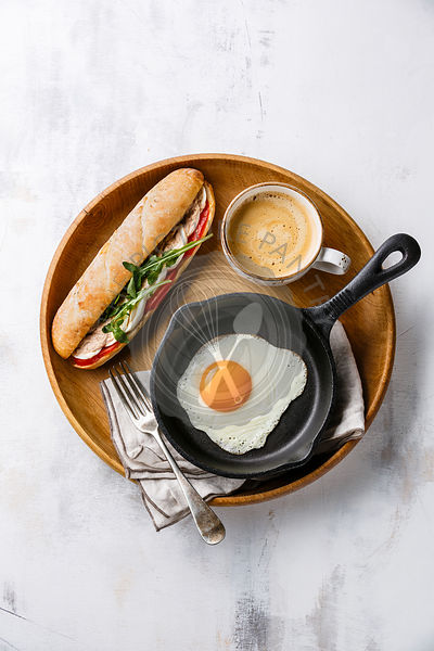 Breakfast with sandwich with tuna and egg, fried egg on iron pan and coffee on wooden tray on white background