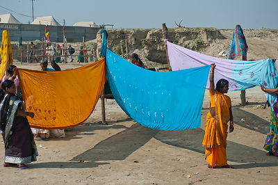 Women pilgrims provide a cover for the other women pilgrims to change after the holy dip in the Ganges during the Kumbh Mela
