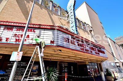 Woman changing letters on movie theater marquee