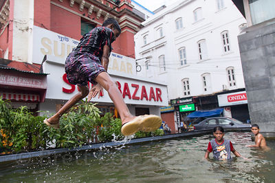 A boys swim in a filthy fountain in Newmarket, Kolkata, India