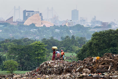 Women work on the top of the 100 foot tall Dhapa dumping ground (landfill), in the distance is Science City, Dhapa, Kolkata, ...