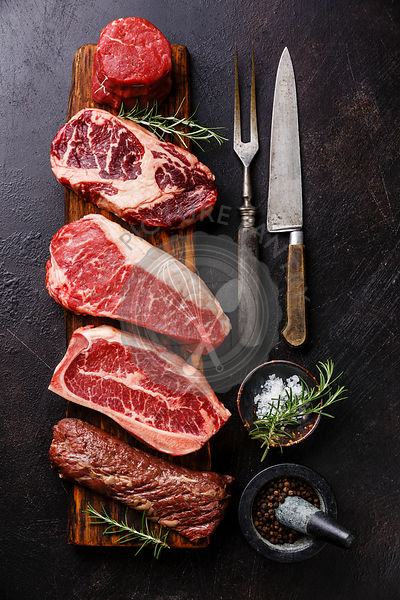 Variety of Raw Black Angus Prime meat steaks Tenderloin fillet mignon, Rib eye, Striploin, Blade, Machete on wooden board and...