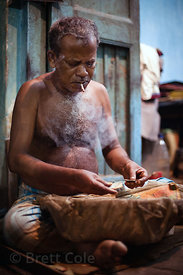A man rolls simple tobacco cigarettes (bidis) in Bowbazar, Kolkata, India.