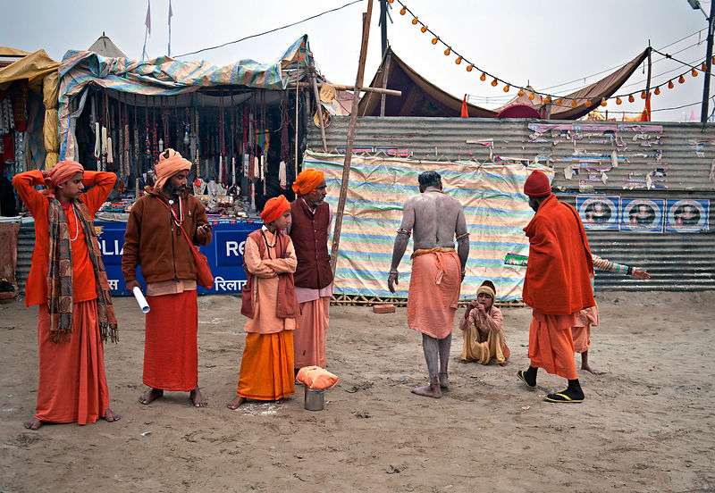 An old saint chats with a boy while others wait for them to finish their conversation. This photograph was shot during the Ku...