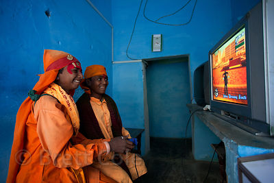 Two boys pretending to be sadhus (holy men) to get money from tourists, playing Grand Theft Auto video game, Pushkar, Rajasth...